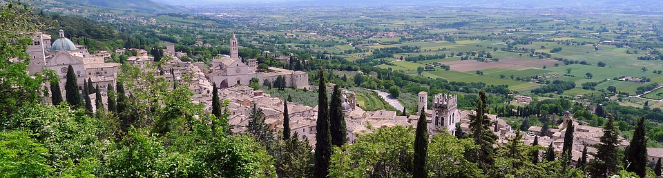A panoramic view of a medieval-style village surrounded by verdant country.