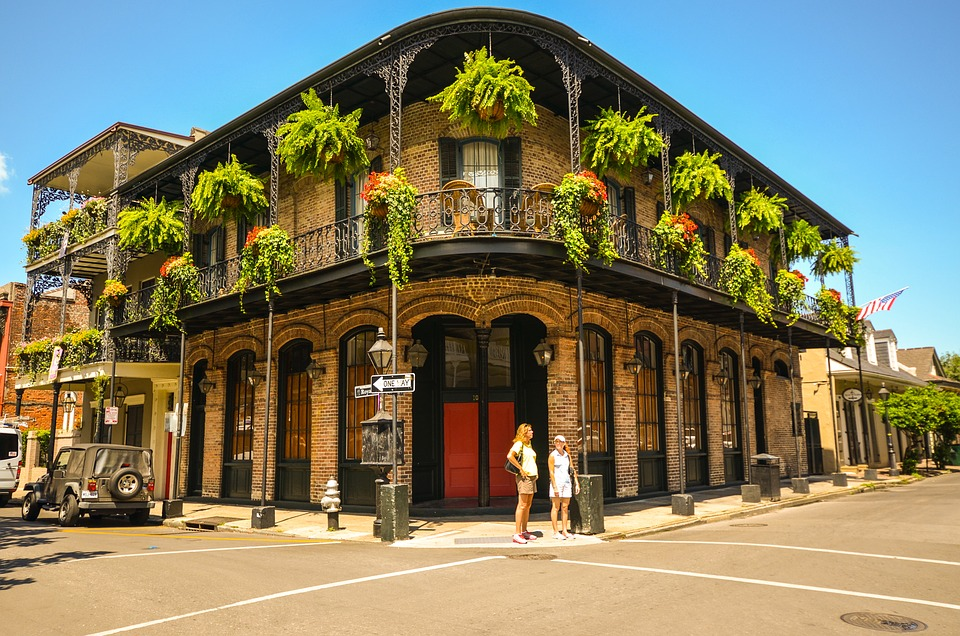 A two level building in New Orleans, Louisiana, United States.  Plants hang from teh second floor, and tourists tand in front.