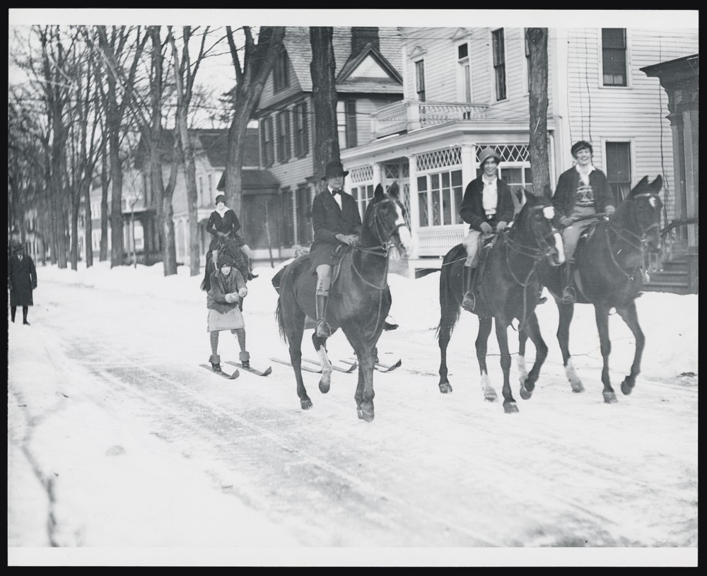 Horseback riders pulling girls on skis down a street
