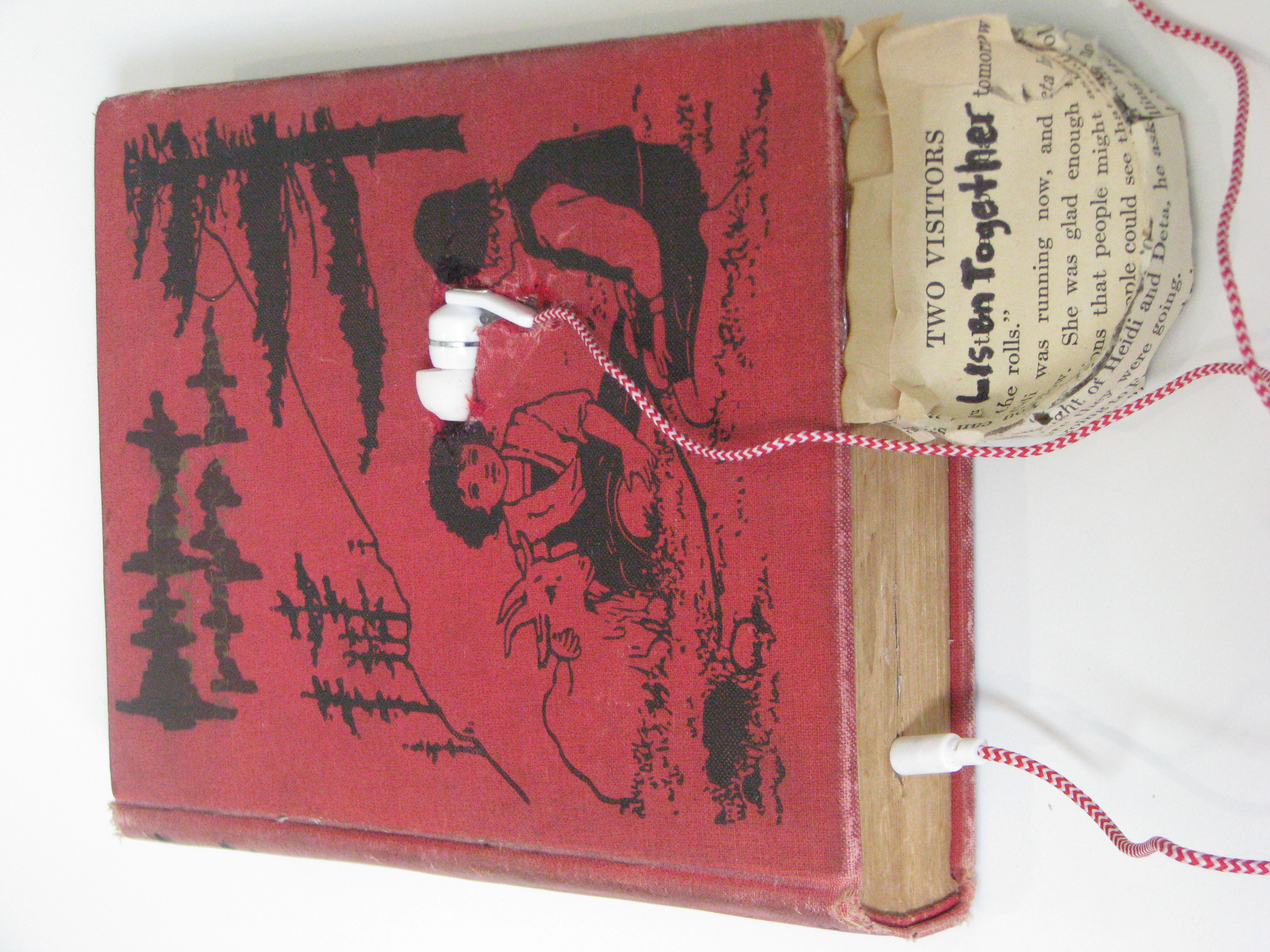 Red book with two children on the cover, in between the children a small hole has been dug into the book where an ear bud has been placed, paper in a circular motion has been added to the bottom of the book the top text reads