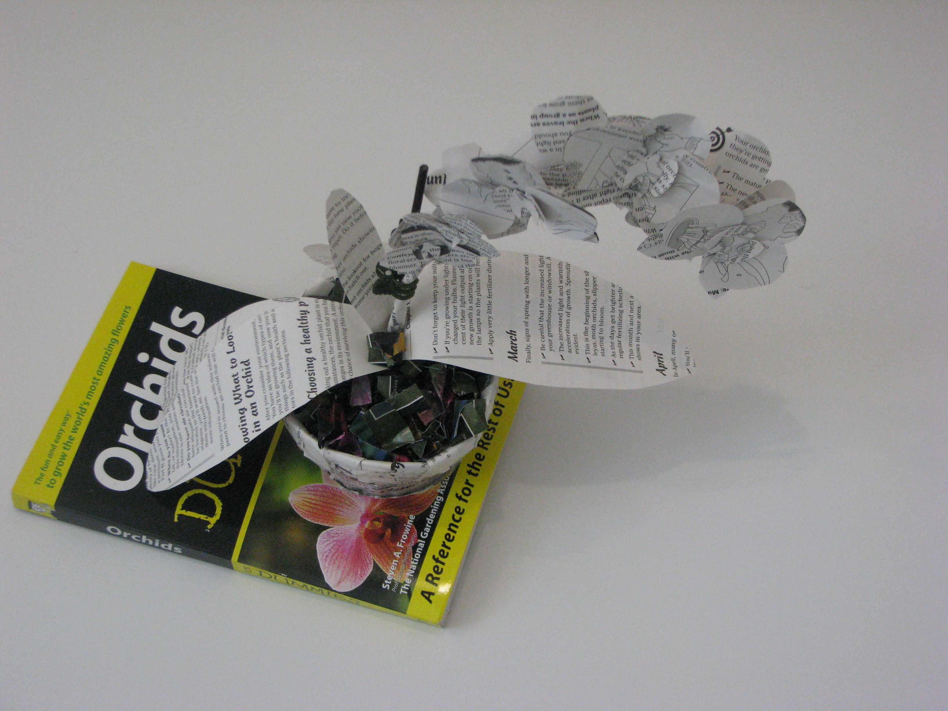 Orchid plant made of book pages sitting in a book page planter that is coming out of the Orchids for Dummies book