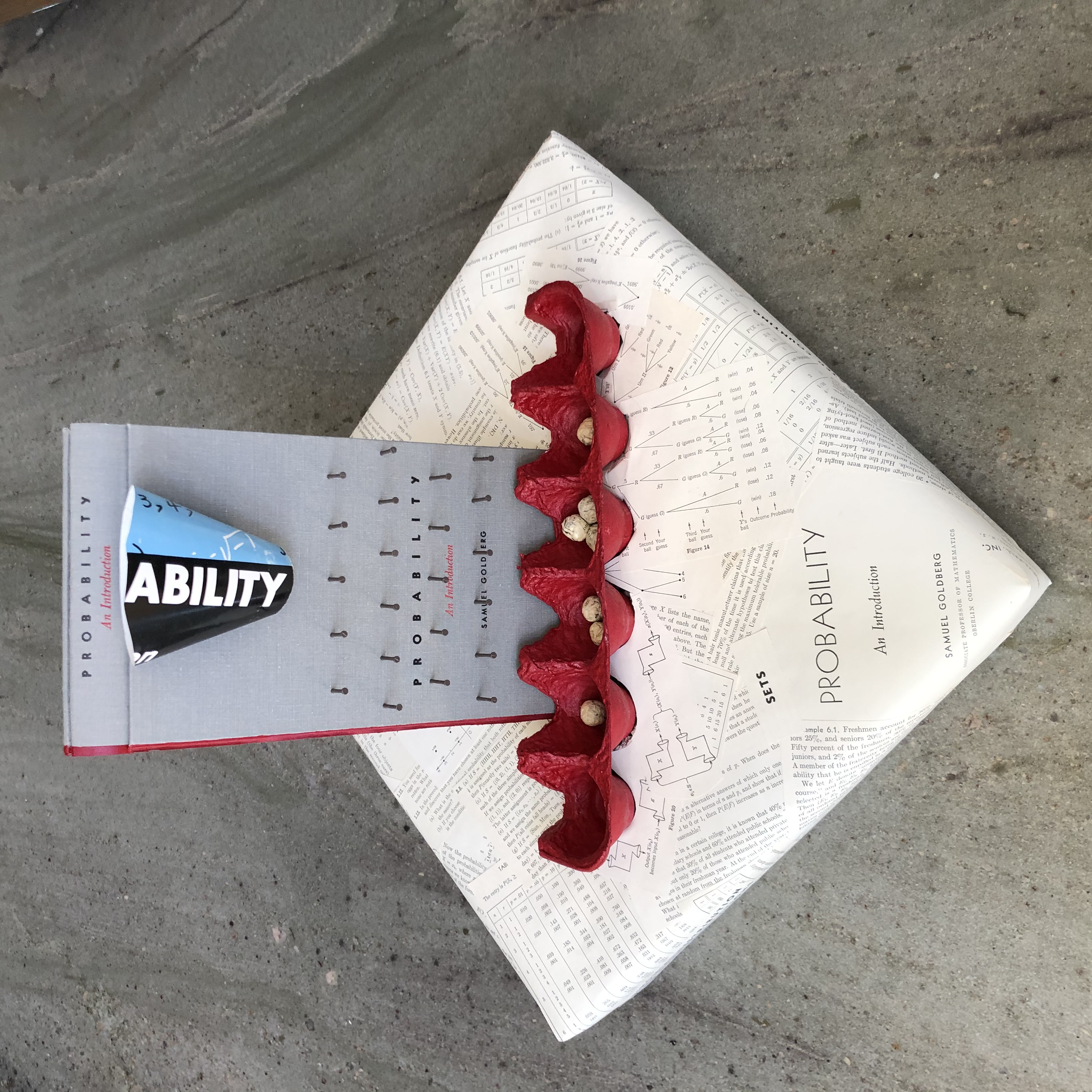 Book that has been turned into a standing peg board where balls can be dropped through a funnel, go through the pegs, and end up in one of several cups