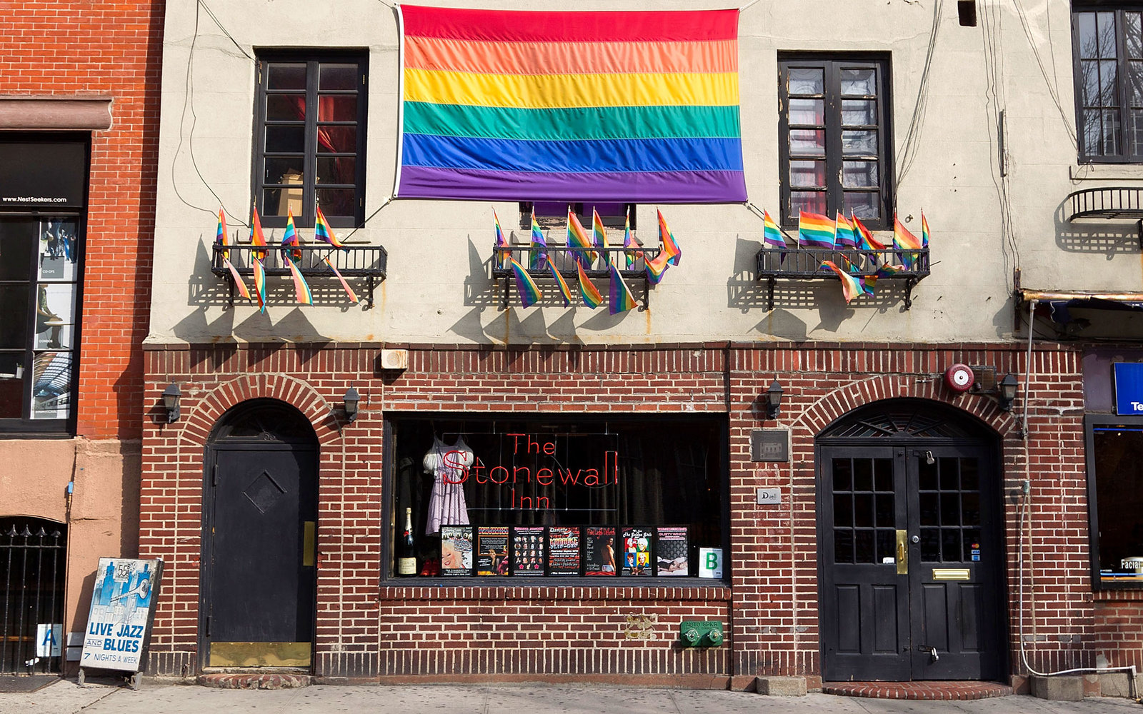 stonewall inn, new york city draped with lgbt flag
