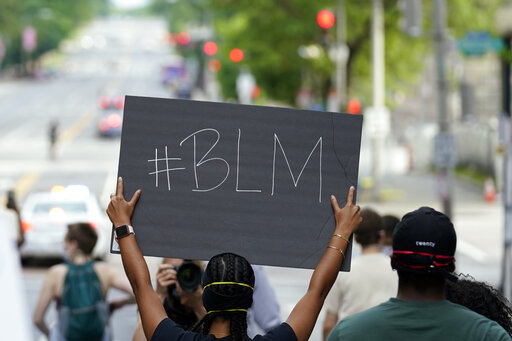 Man from the back holding a #BLM sign as he protests