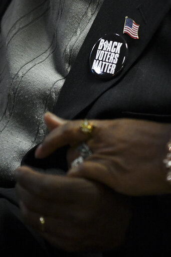 Person wearing a Black Lives Matter button greeting someone else with a warm handshake
