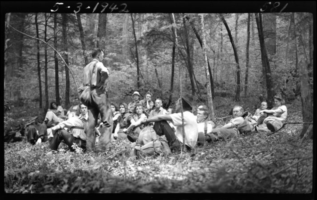 Black and white photograph of Arthur Stupka (standing) lecturing to the Smoky Mountains Hiking Club (sitting and lounging) in the smokies.