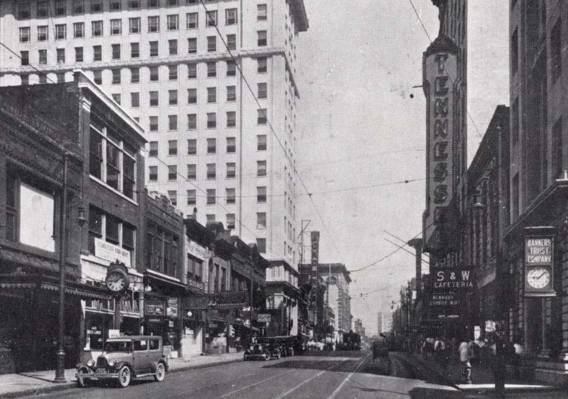 Black and white photograph looking north into Gay Street's 600 Block. the Tennessee theater's sign is visible.