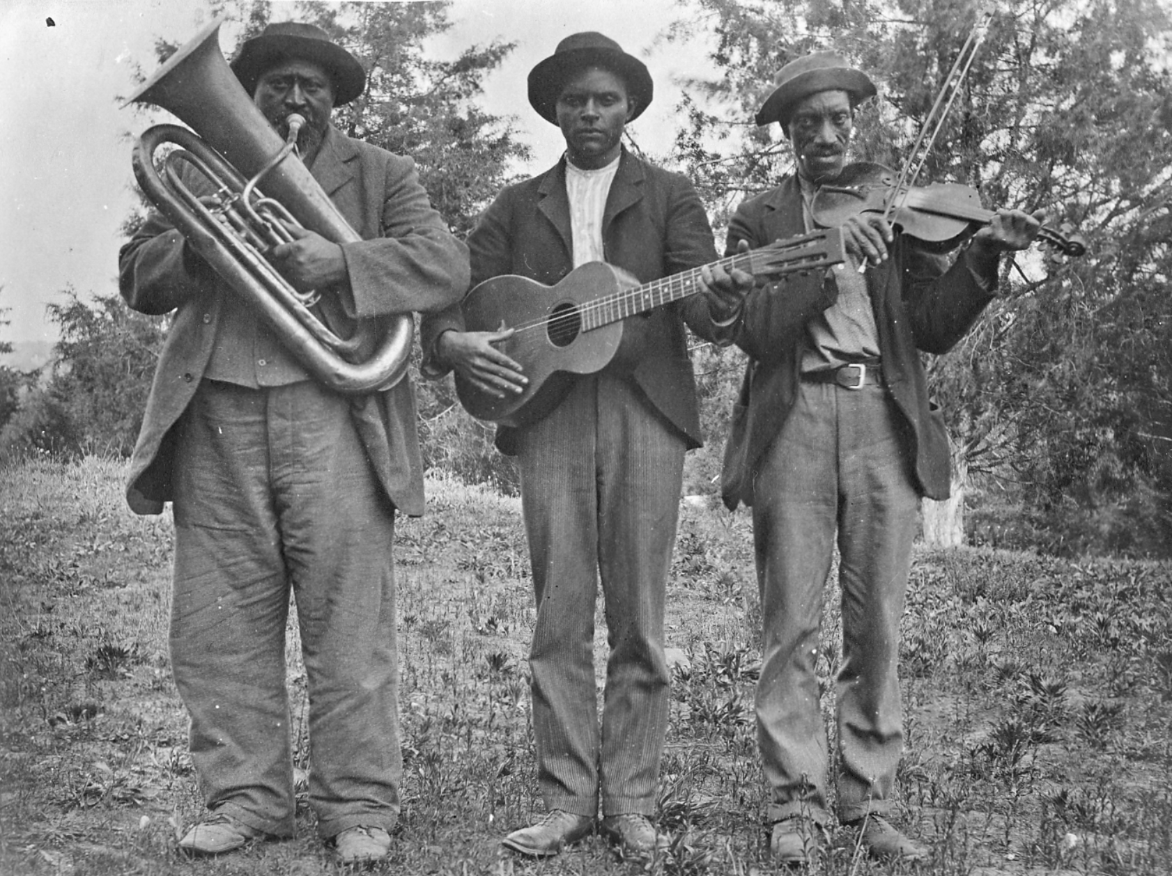 Three African American men are standing holding instruments - a tuba, guitar, and fiddle with a bow.