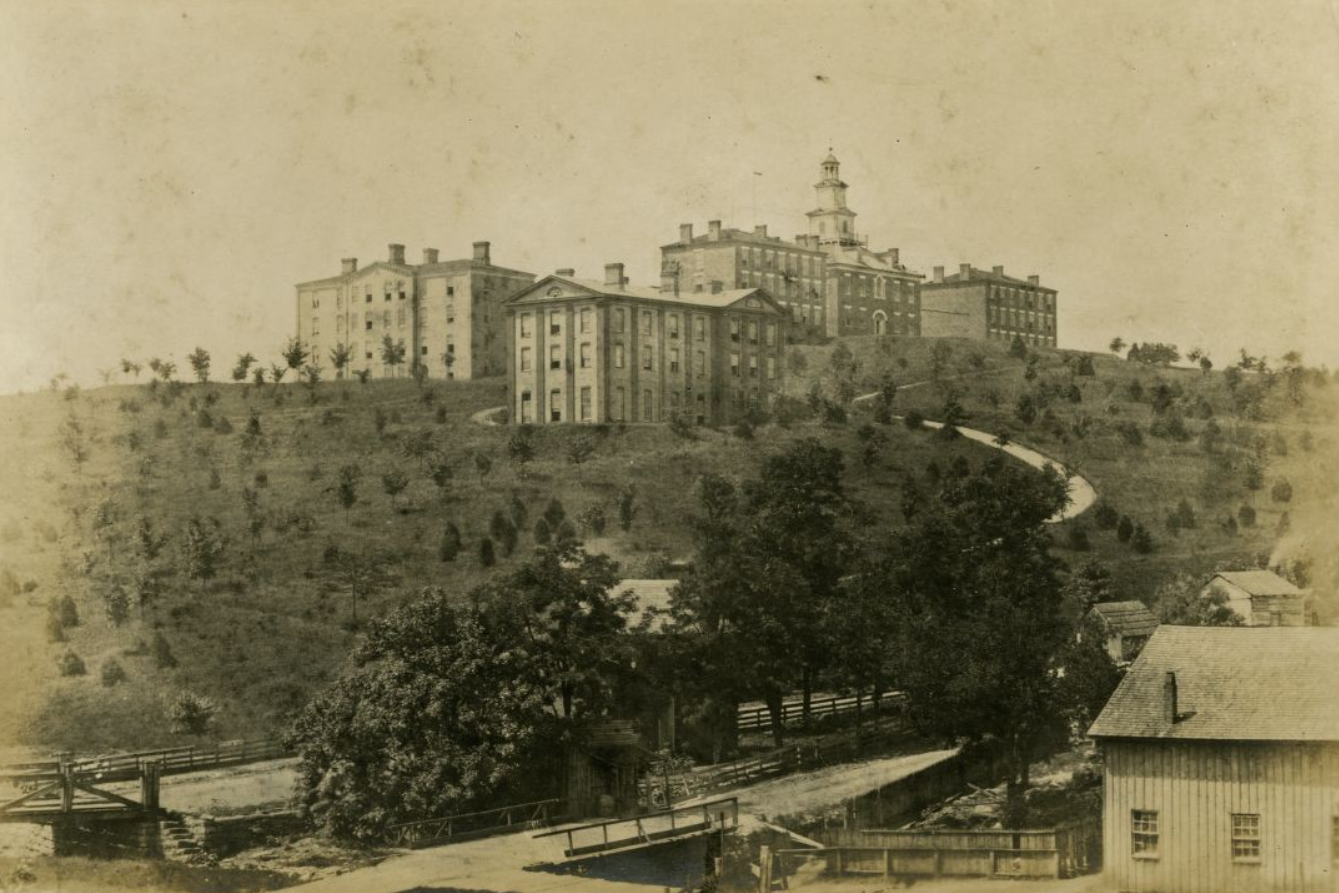 """Sepia photograph of the University of Tennessee's """"Hill."""" Visible are Old College, North College, South College, Main Street, and Cumberland Avenue."""
