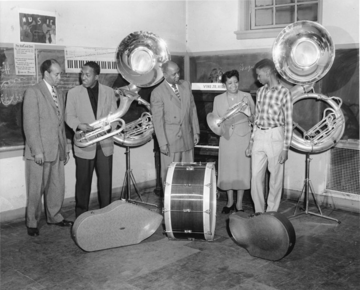 Black and white photograph of L-R: Band Director, S.C. Cobb; unidentified; Principal Leonard A. Jackson; music teacher, Arnetta G. Wallace, and a student.