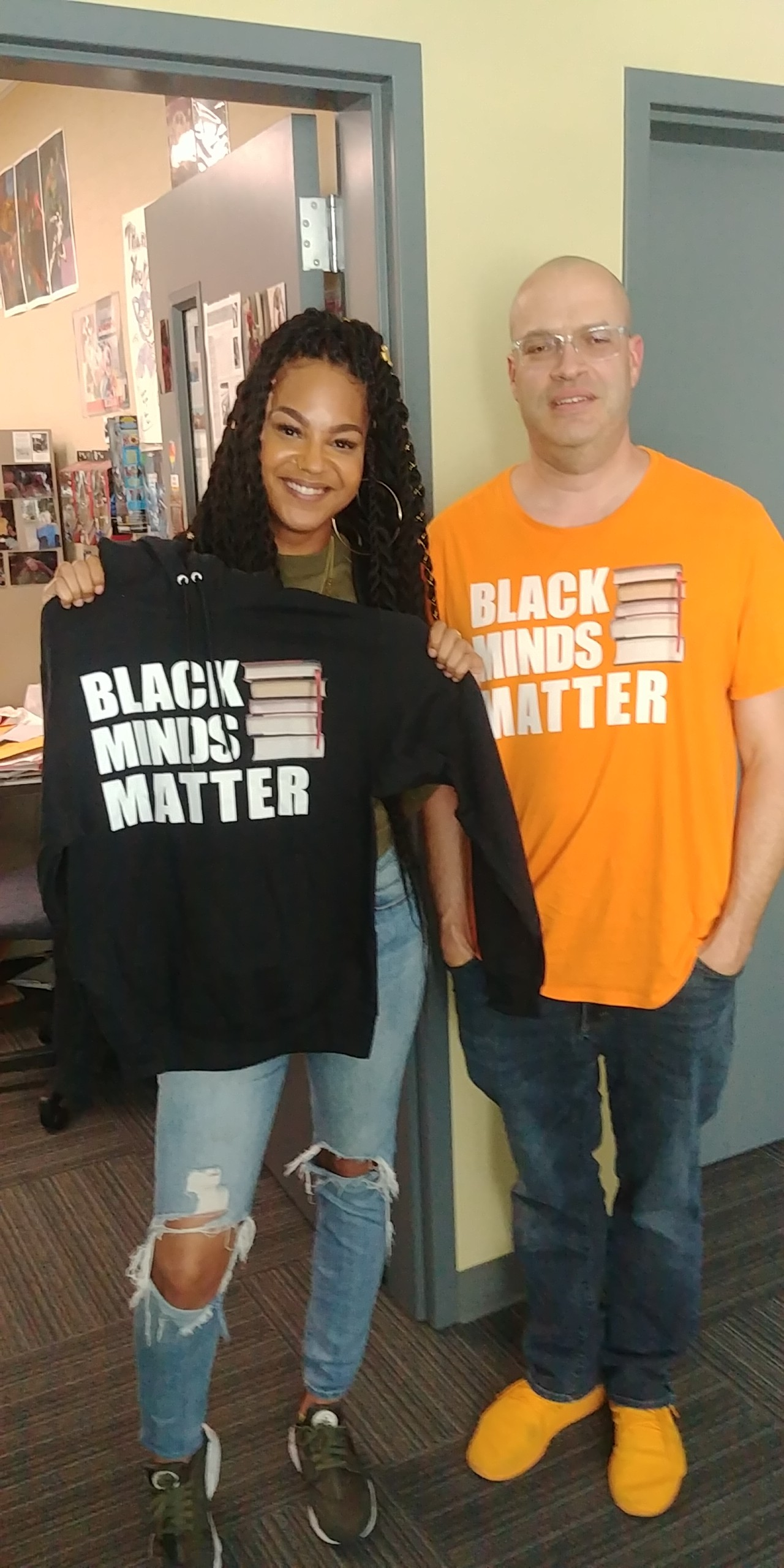 ARC student Grace and librarian David in the ARC Library wearing black minds matter shirts.