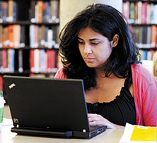 Graduate HCOM student studying in the library