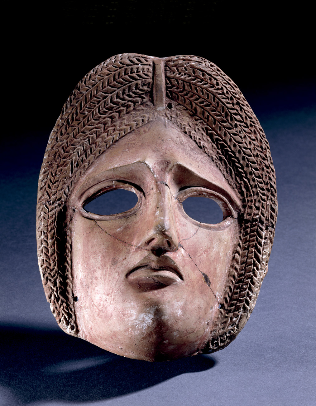 Terracotta tragic mask, representing a female character with arched brows; Roman, 1st – 2nd century AD.
