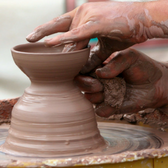 Photo of hands sculpting clay on a pottery wheel