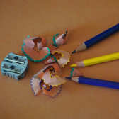 Photo of colored pencils with a handheld sharpener, with shavings