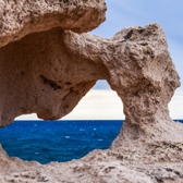 Photo of rock arch by ocean