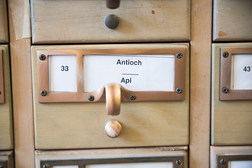A close-up image of a card catalog drawer with brass fixtures.