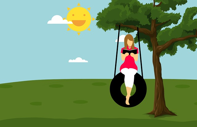 Girl sitting on tire swing reading in the sun.