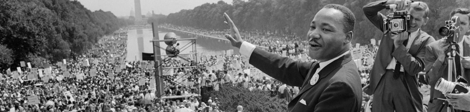 Martin Luther King, Jr. at the March on Washington, August 1963. He is smiling. Newsmen are taking photographs.