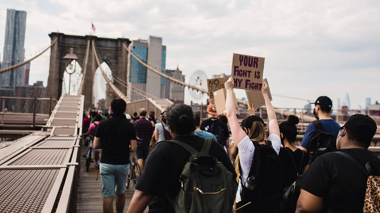 Stock image of protesters crossing a bridge