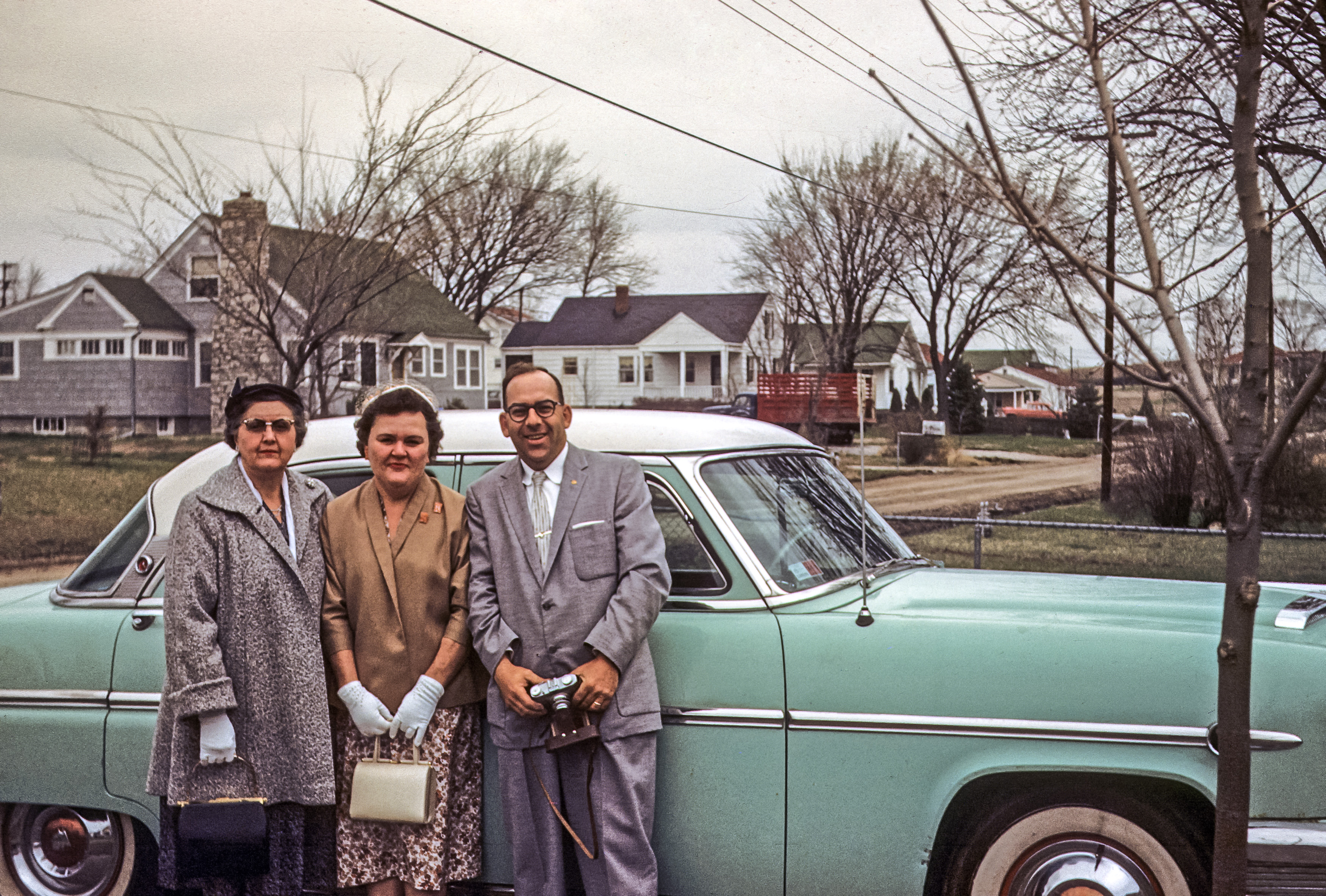 Vintage photo of a family standing near a car in the 1950s