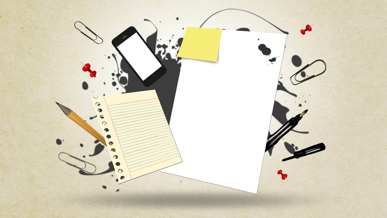 a picture of paper, ink, a phone, and other writing supplies