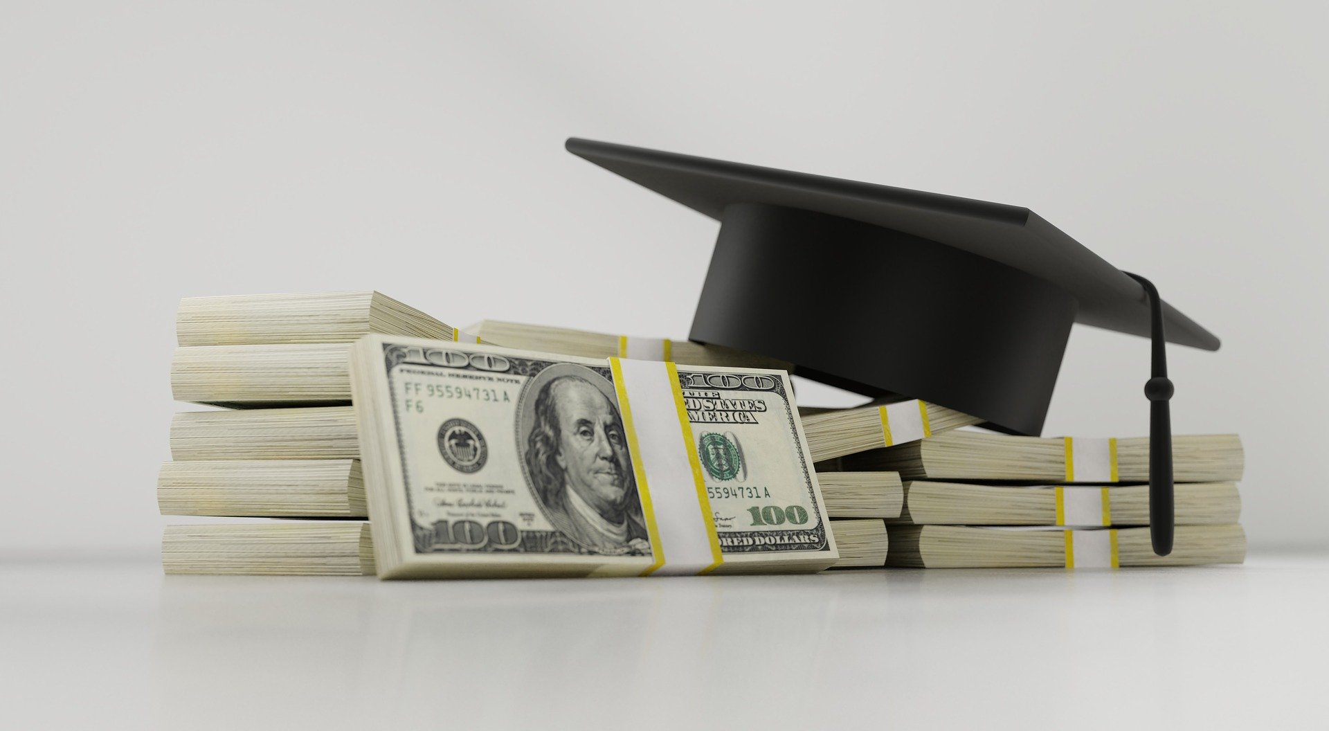 An image of stacks of money and a mortarboard (graduation) cap.
