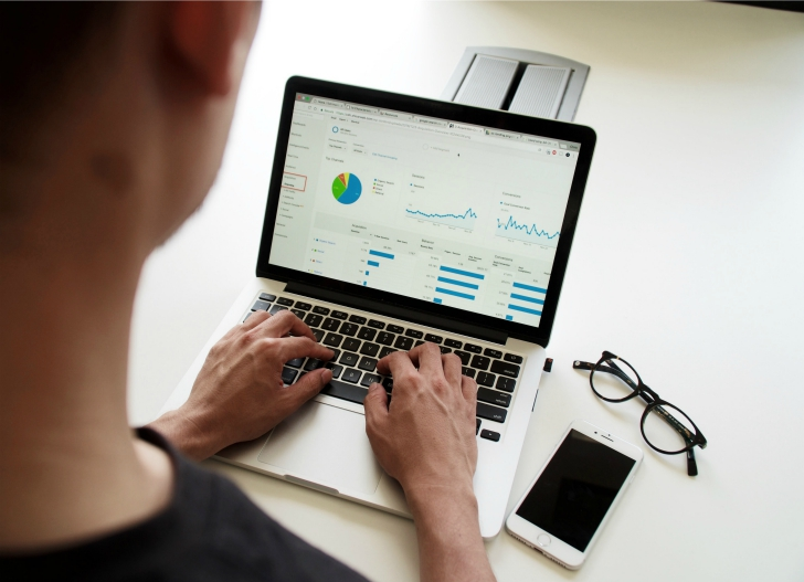 man looking at laptop with graph and pie chart
