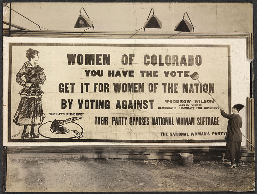"Photograph of unidentified woman putting up billboard with bucket and broom. Billboard reads: ""'Women of Colorado, you have the vote. Get it for women of the nation by voting against Woodrow Wilson and the Democratic Candidate for Congress. Their party opposes national woman suffrage. The National Woman's Party."" Billboard features image of young woman and a hat with ""The Woman's Party"" feather and a ""50-50"" price tag, above which is the motto ""Our Hat's in the Ring."""
