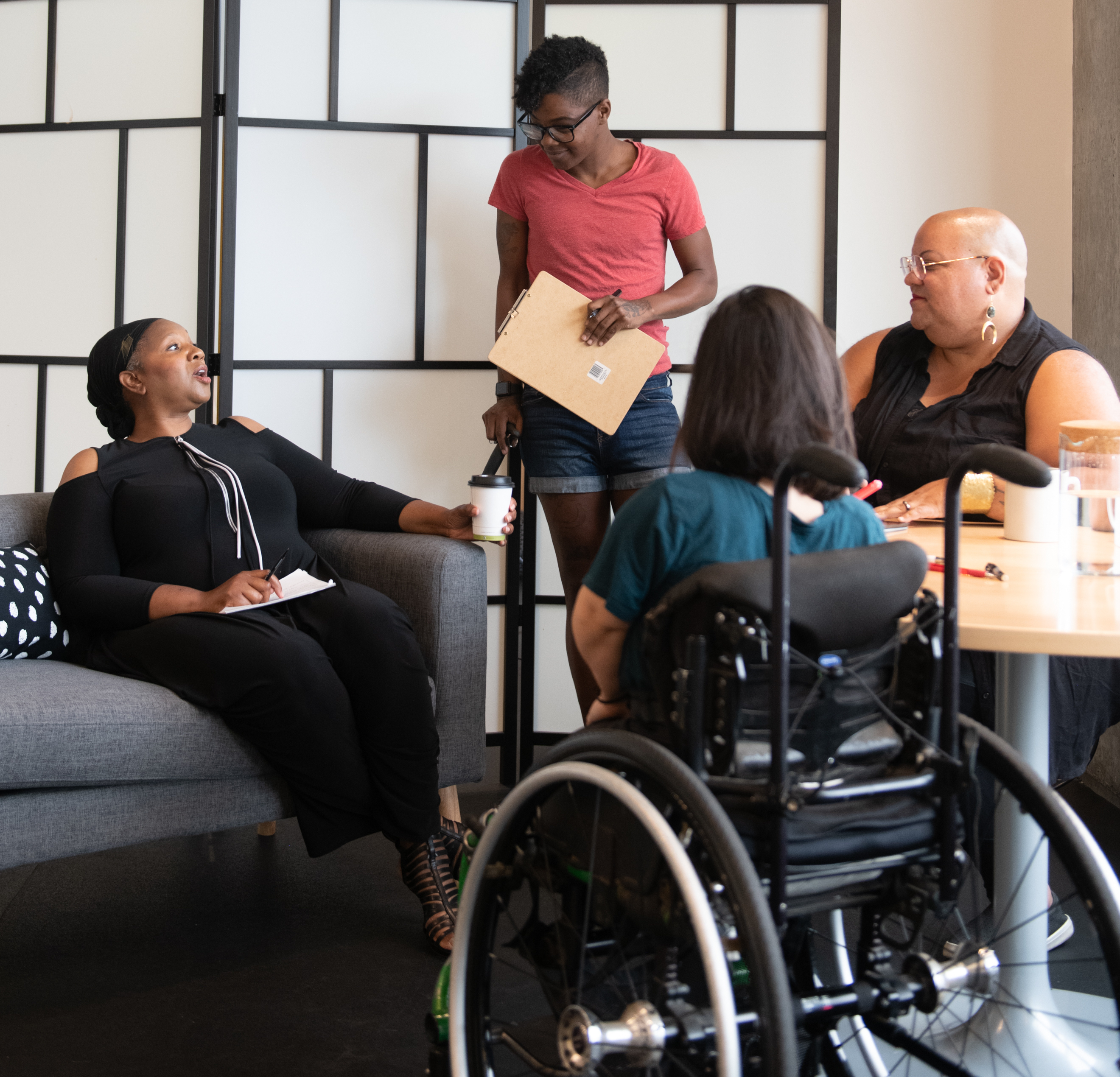Four disabled people of color gather around a table during a meeting