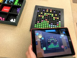 Bloxels; The Bloxels pieces, game board with a game built on it in pieces, and an iPad snapping a picture of the gameboard to be used in the Bloxels app to play a video game