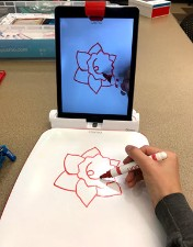 Osmo Masterpiece; Osmo Masterpiece set up. An iPad is on a table and in the Osmo base. It shows the outline of a flower projected onto its image of the whiteboard below. The Masterpiece whiteboard is set up on the table directly in front of the ipad and someone is drawing the outline of the flower by watching the screen as they draw.