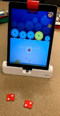 An iPad and number tiles below it. The iPad is set up in the Osmo base with the reflector over the camera. On the screen is the Osmo Numbers game, with numbers pictured in circles for students to add up on tiles to make the circles pop and disappear. The dice tiles incorrectly count up the highlighted number on the screen