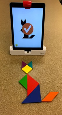 An iPad and tangram tiles set up to play the Osmo Tangram game. The iPad screen has a black geometric image of a sitting cat and the tangrams are set up to build the shape on the screen. A check mark is on the screen because the shape was built correctly with the tangram tiles