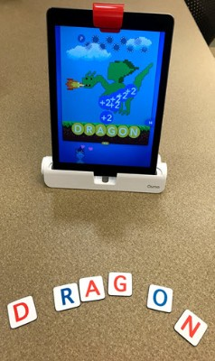 An iPad and word tiles set up to play the Osmo Words game. On the iPad screen is a dragon and the word dragon is spelled out on letter tiles below