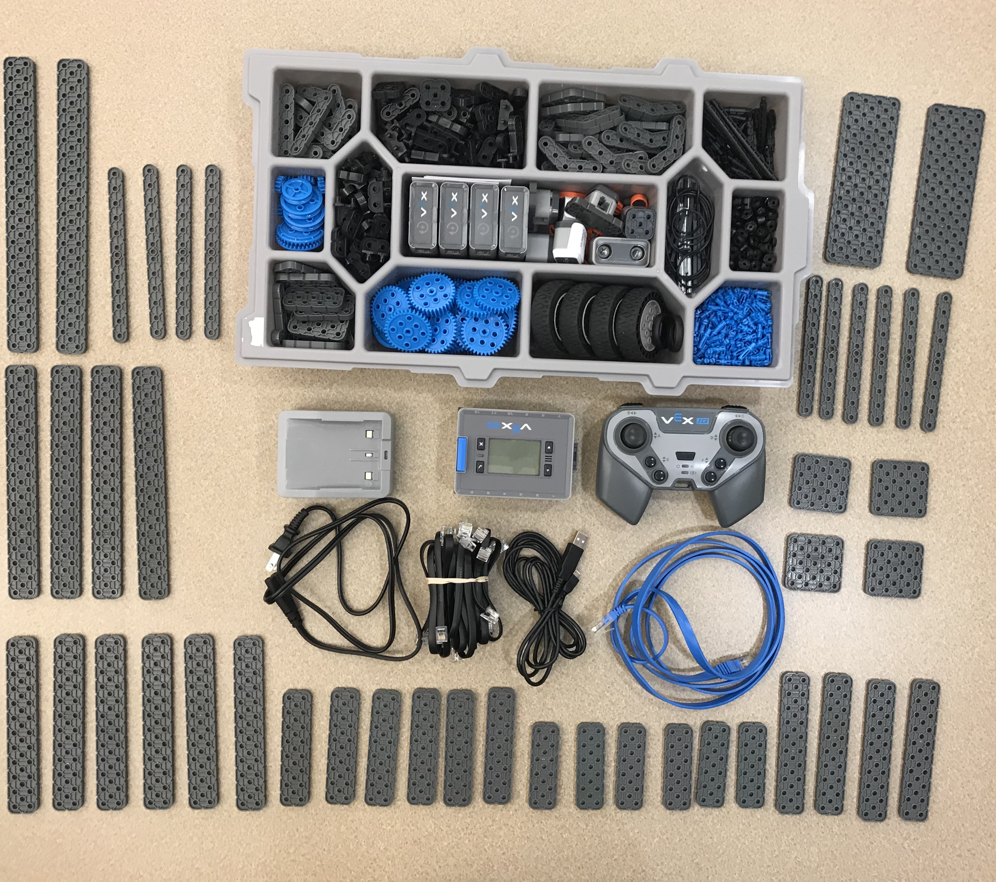 Parts of the Vex IQ Super Kit laid out unassembled including wheels, connectors, platforms, batteries, controllers, wires, and control centers