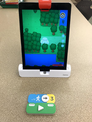 "Osmo Code picture of iPad set up to play. On the screen is the game where students move the character using coding tiles that come with the game. The coding tiles are laid out in front of the iPad so that the reflector connected to the iPad camera connected to the iPad will see them. The tiles give coding commands for ""go"" and ""forward three spaces"""