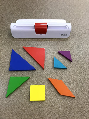 What comes in the Osmo Tangram kit: an Osmo base for an iPad, a large blue triangle tangram, a large red triangle tangram, a medium green triangle tangram, a small blue and a small purple triangle tangram, a yellow square tangram, and an orange rhombus tangram
