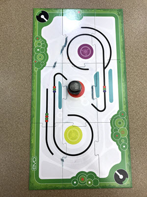 Ozobot sitting in the middle of the game board, which has paths and commands for the bot to follow