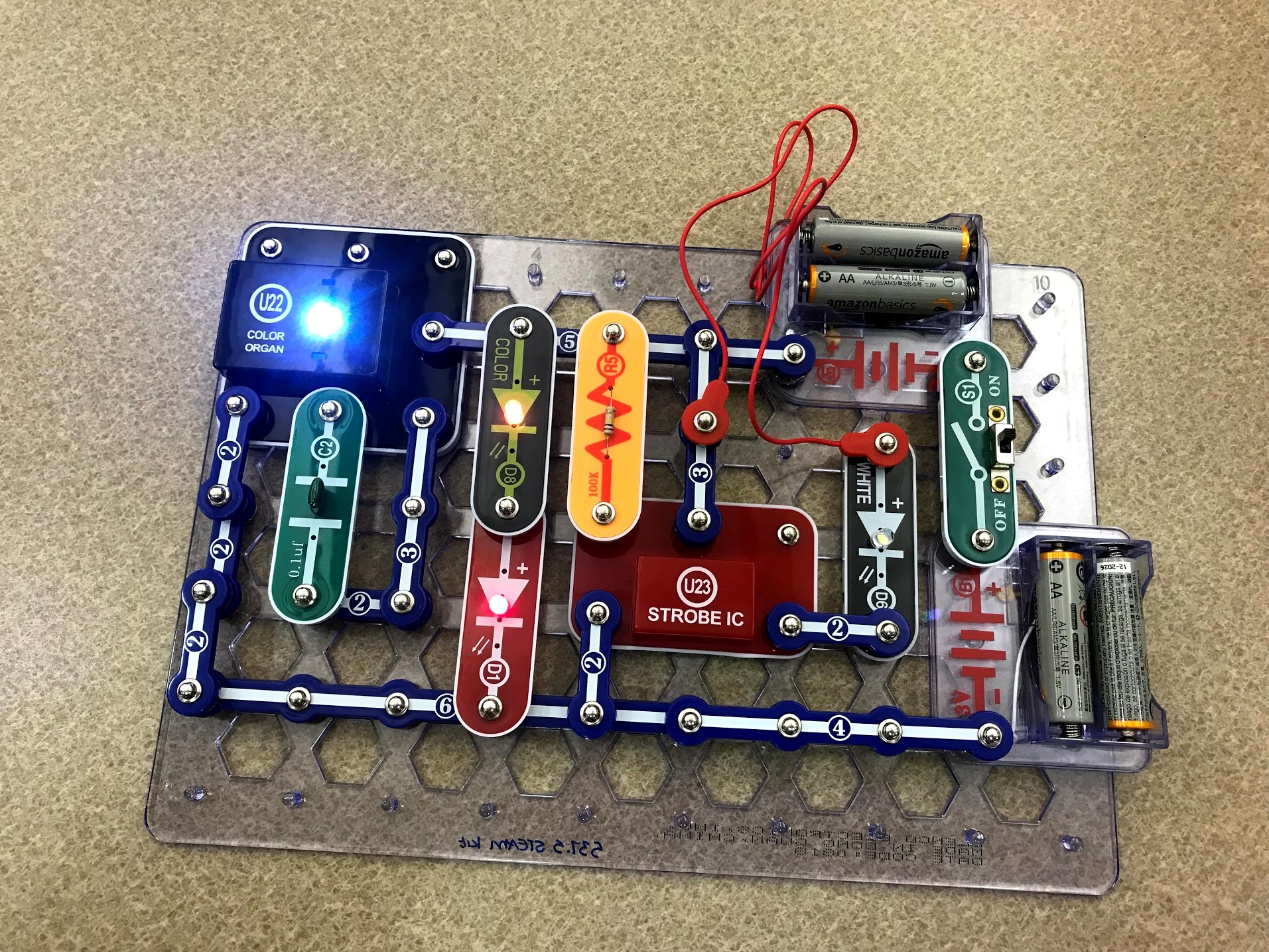 A constructed snap circuit. Several conductive parts are connected so that multiple LEDs are lit up.