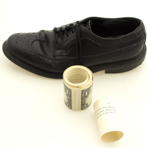 A black shoe with rolled bills next to it