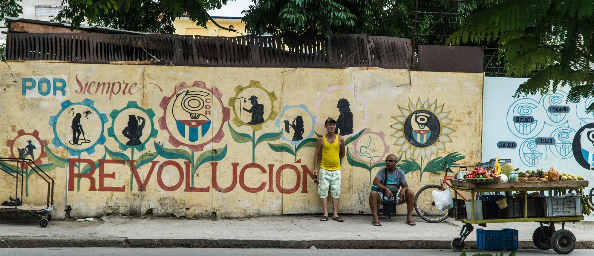 Two men in front of a mural that says Por Siempre Revolucion