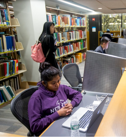 Student studying at a Bobst Library study carrel with book shelves in the background.