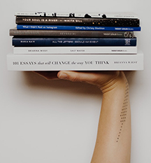 A stack of 6 books held up by a hand.