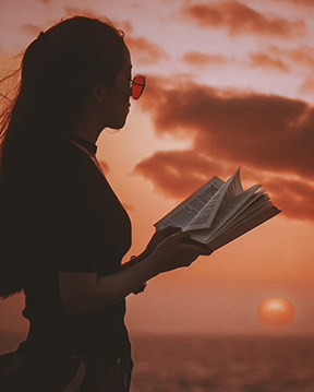 Woman holding book; sunset sky.
