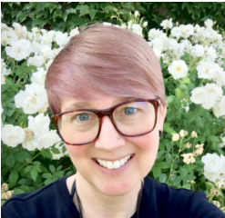 Librarian Silke Higgins in front of a bush with white flowers and green leaves