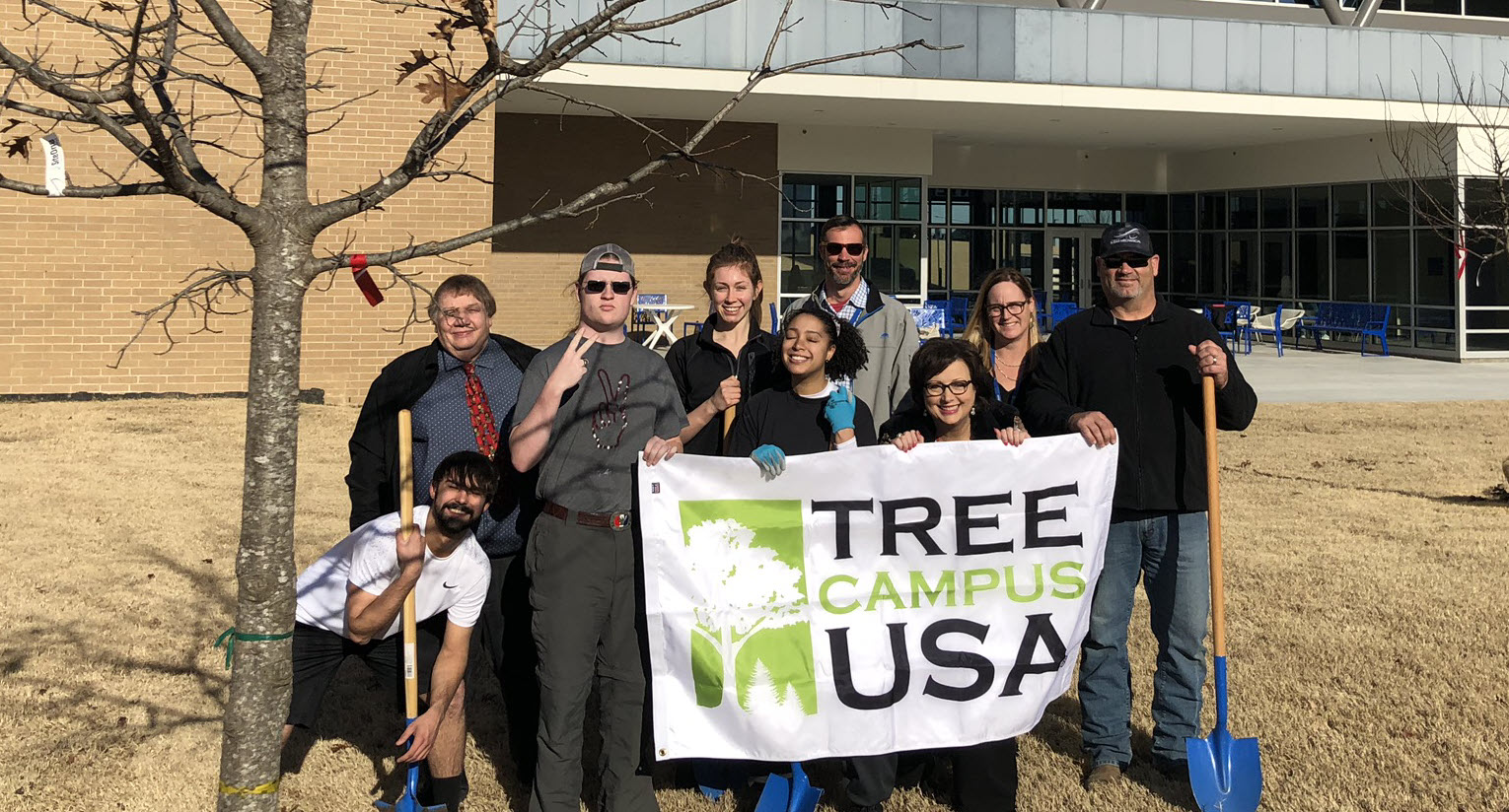 Photo of Southeast Campus students, staff, and faculty with the Tree Campus USA banner