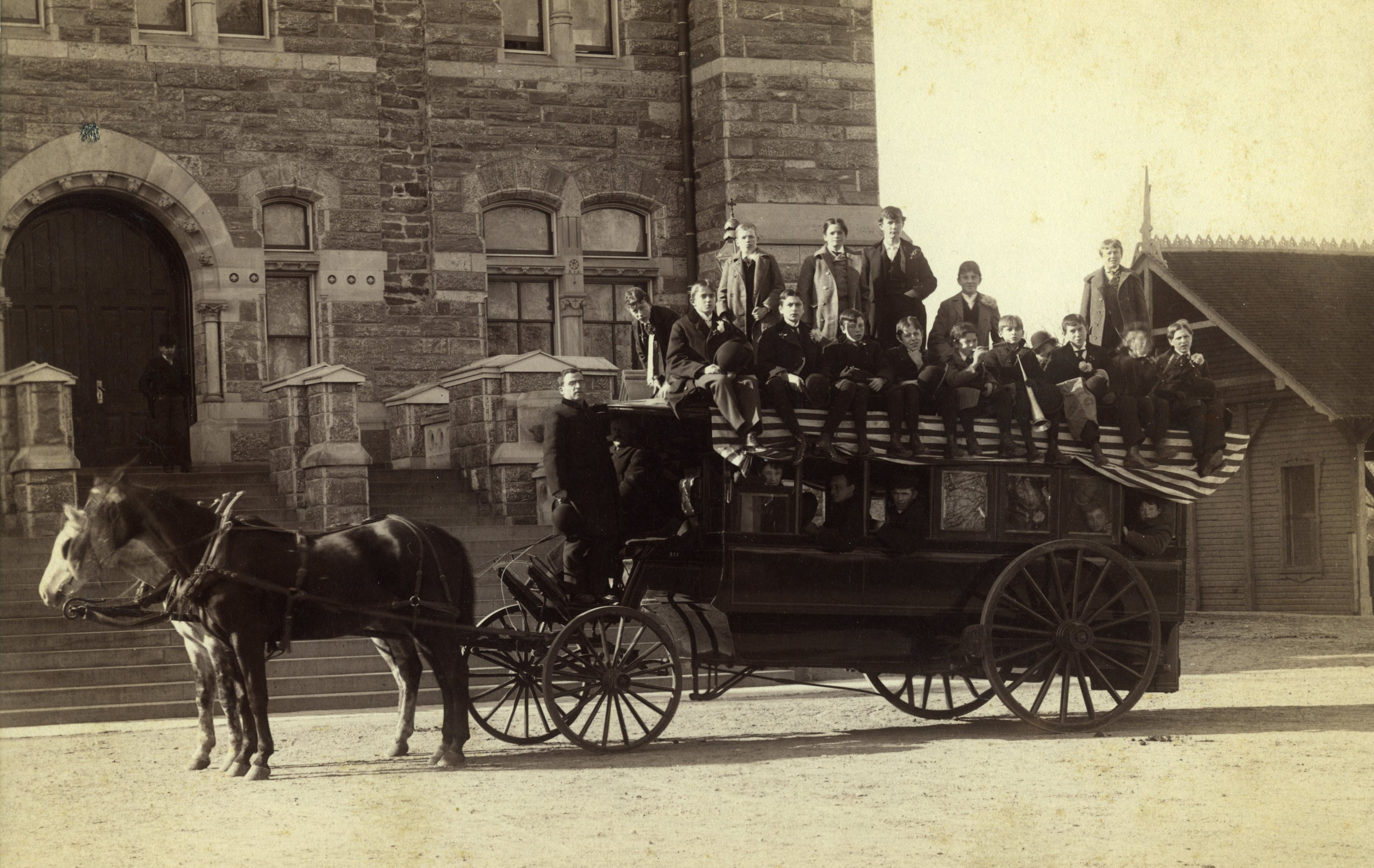 Students in horse-pulled carriage outside Healy Hall waiting to go to a baseball game