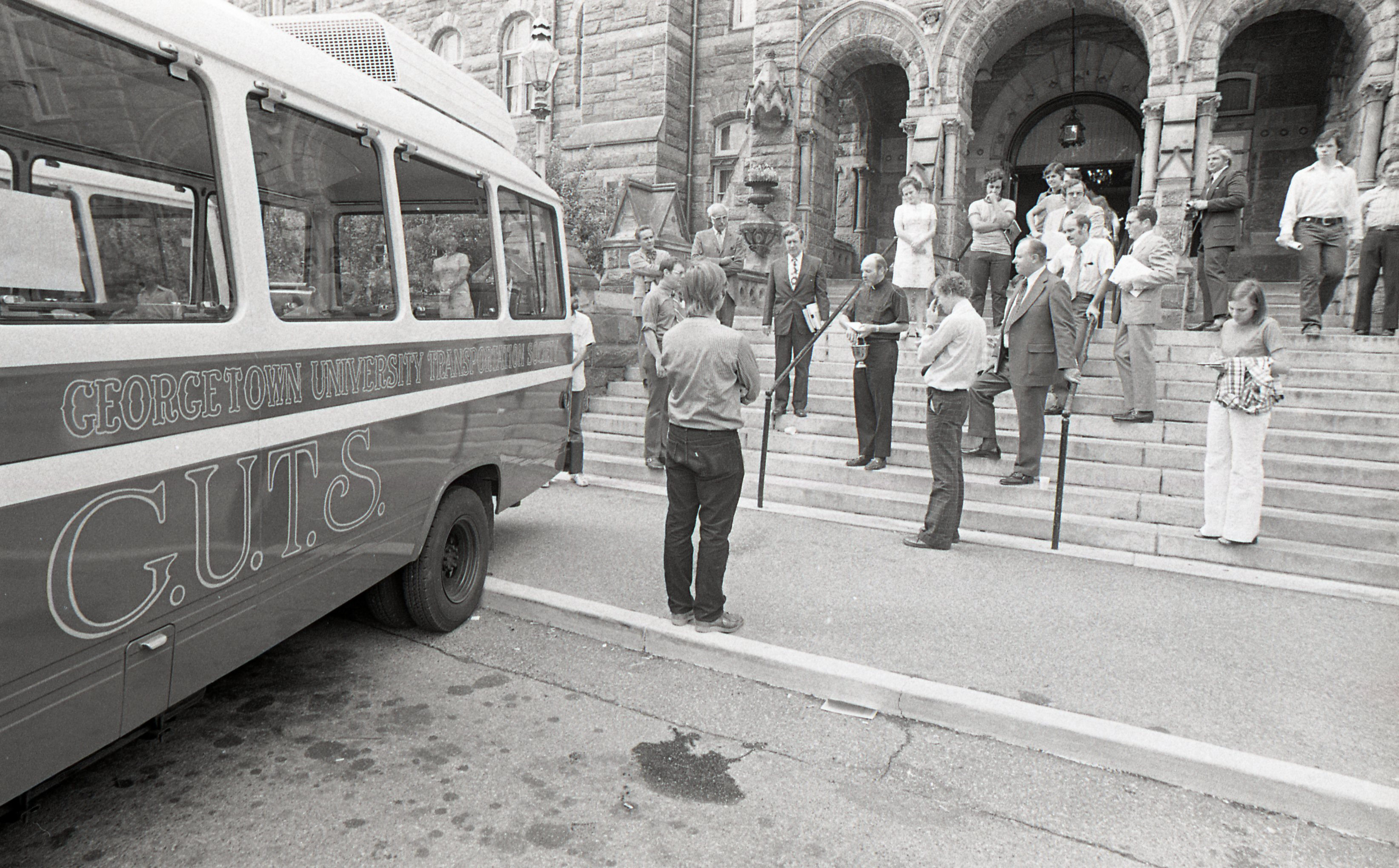 GUTS bus outside Healy Hall with waiting passengers
