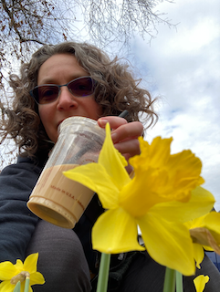 Annie drinking local boba tea with an early daffodil flower